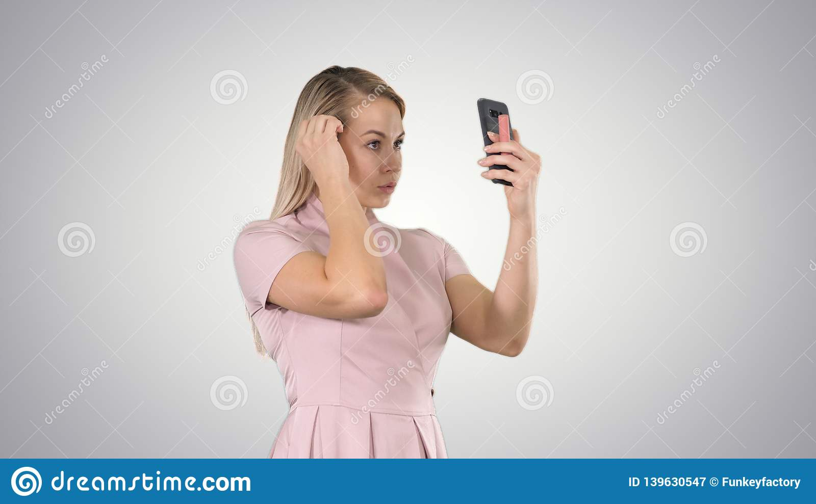 Blonde woman preening in front of the smartphone on gradient background.