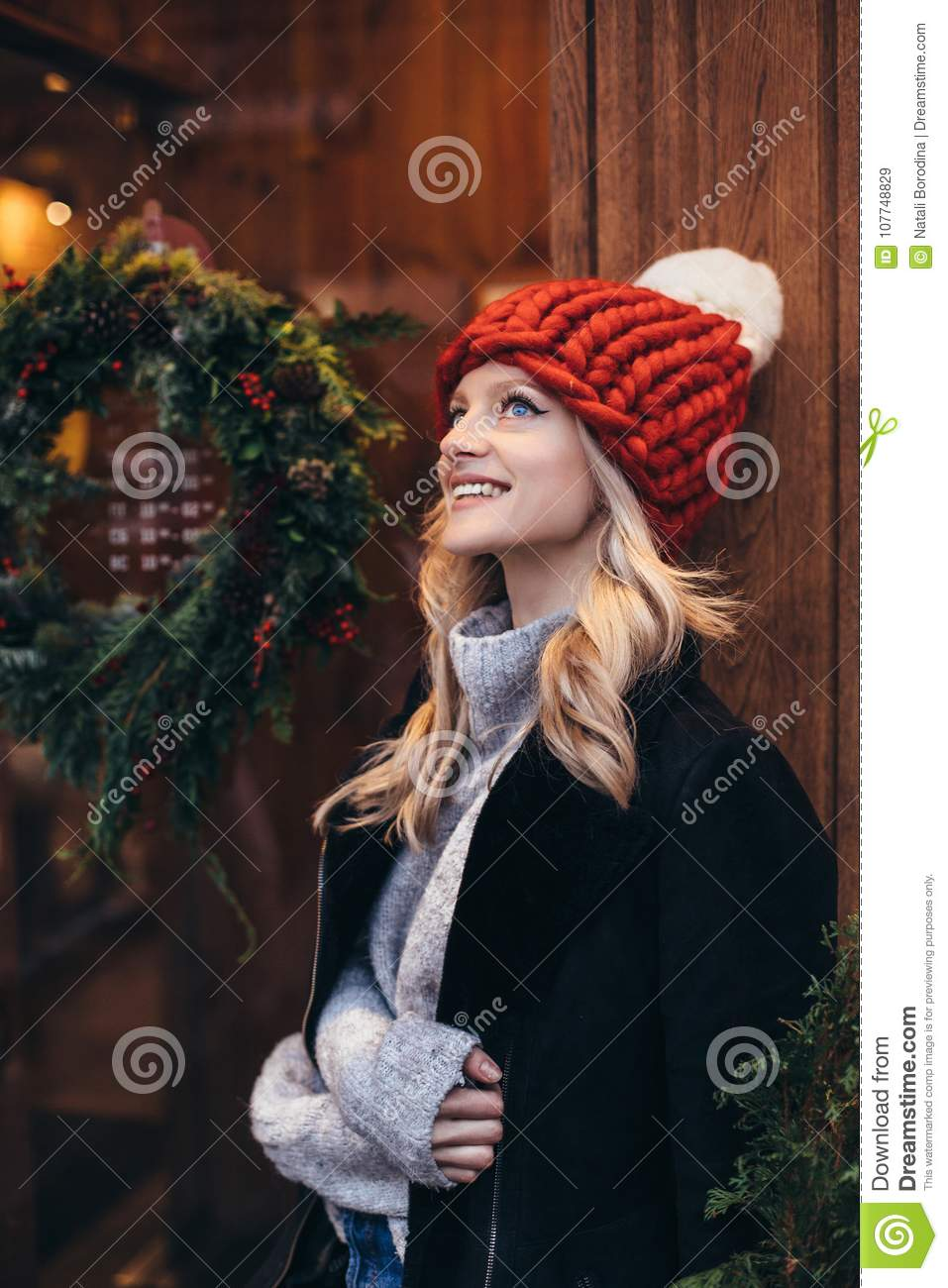 Young Blonde Woman In Red Knitted Hat With White Pompon Grey Sweater Black Jacket And Blue Jeans Make Posing With Christmac Cafe Window On The Background