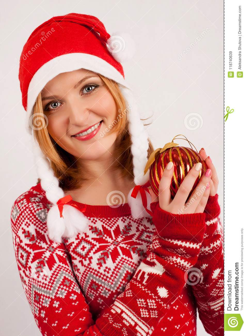 Blonde woman in red New Year`s sweater and New Year`s cap on white background holds Christmas tree ball