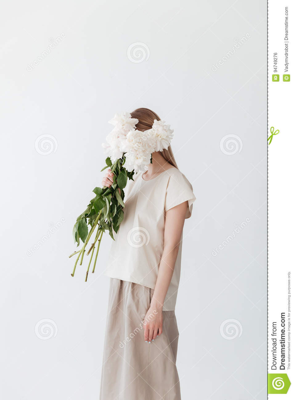 f500162b645 Image of amazing blonde woman standing isolated white background holding  flowers. Looking aside.