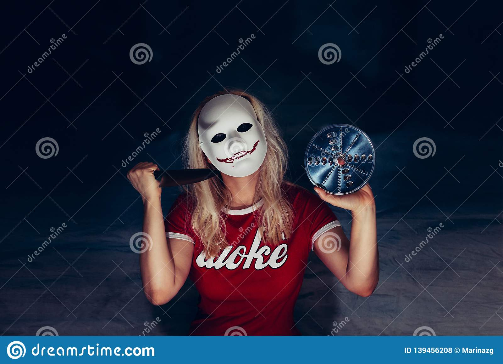Blonde woman under white mask with spooky bloody smile, holding knife