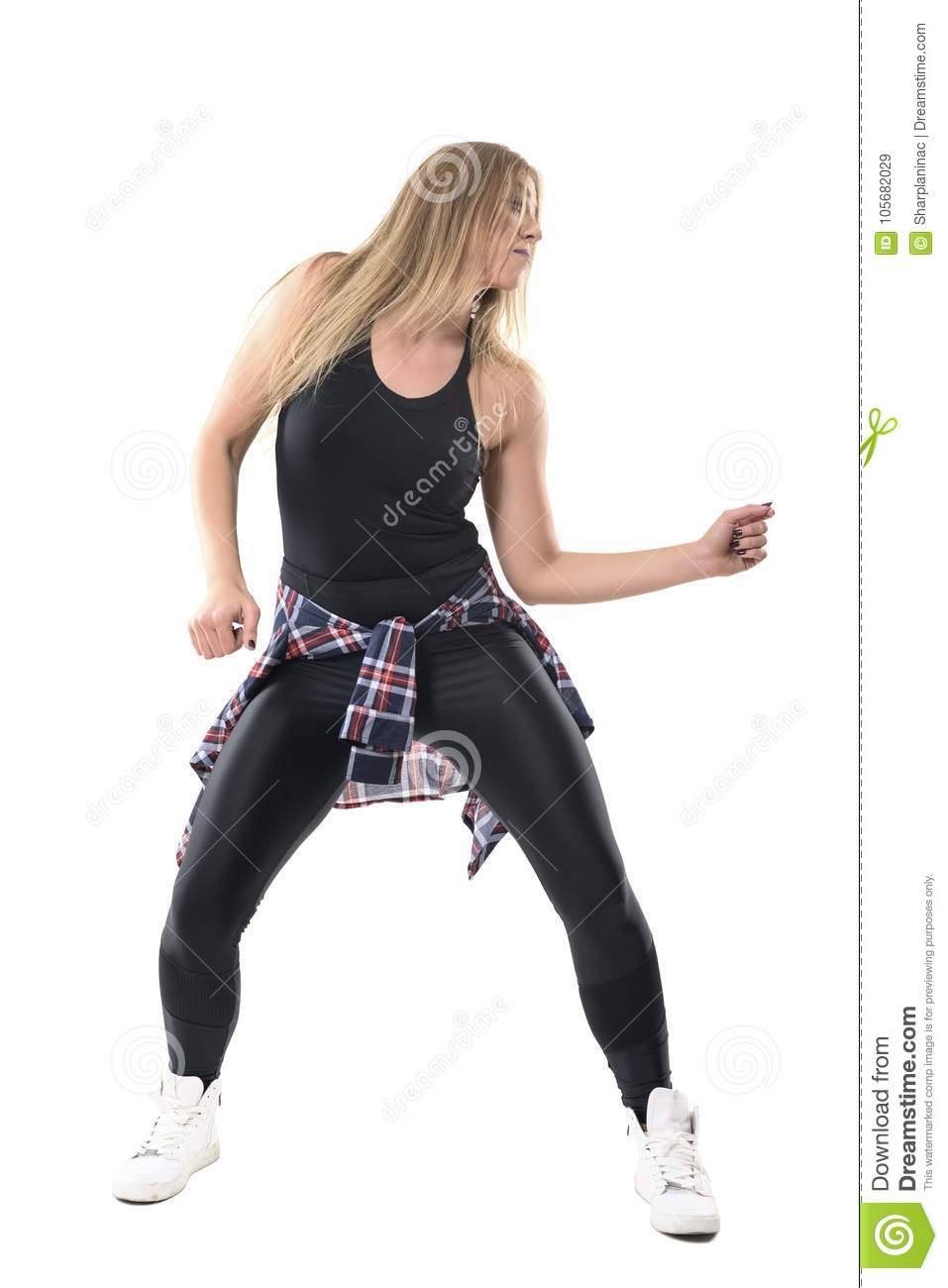 Blonde young woman dancing dancehall aerobics and moving arms looking away. Front view.