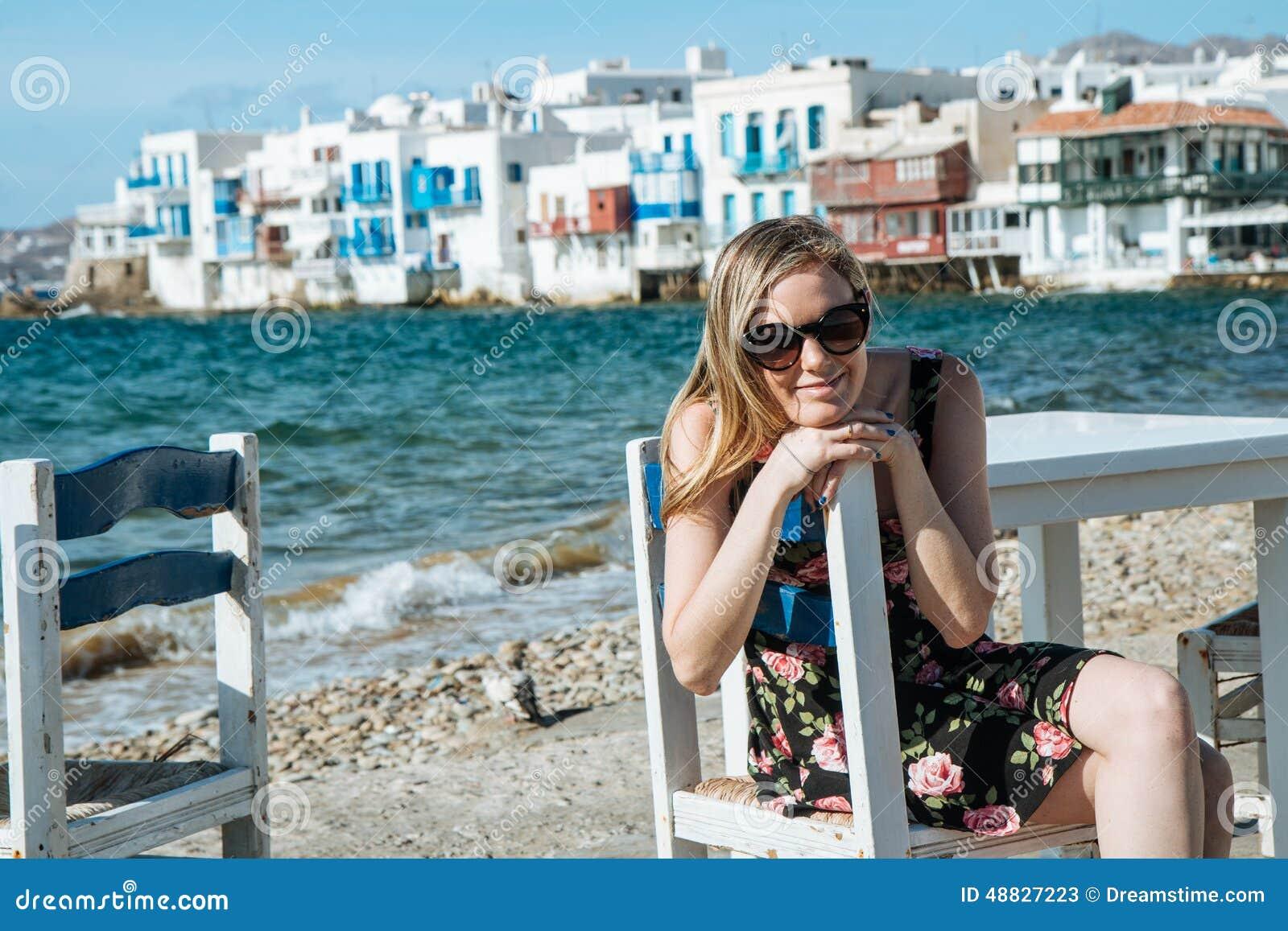 Blondemeisje die met zonnebril op een stoel bij het strand zitten