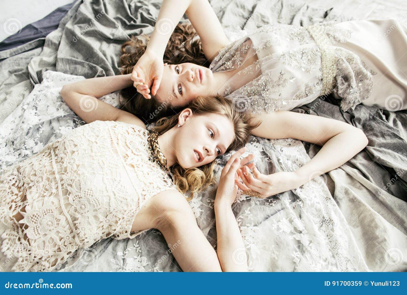 Blondes gelocktes Frisurmädchen der hübschen Zwillingsschwester zwei im Luxushausinnenraum zusammen, reiches Konzept der jungen L