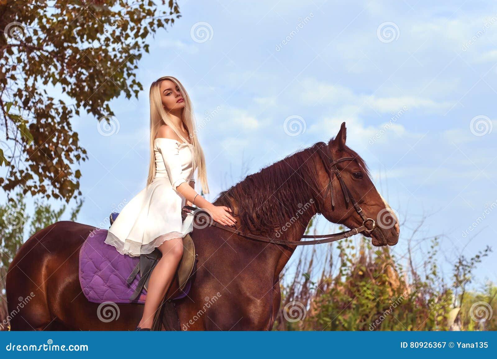 Blondes kaukasisches Mädchen, das ein Pferd an einem warmen und sonnigen Sommertag reitet