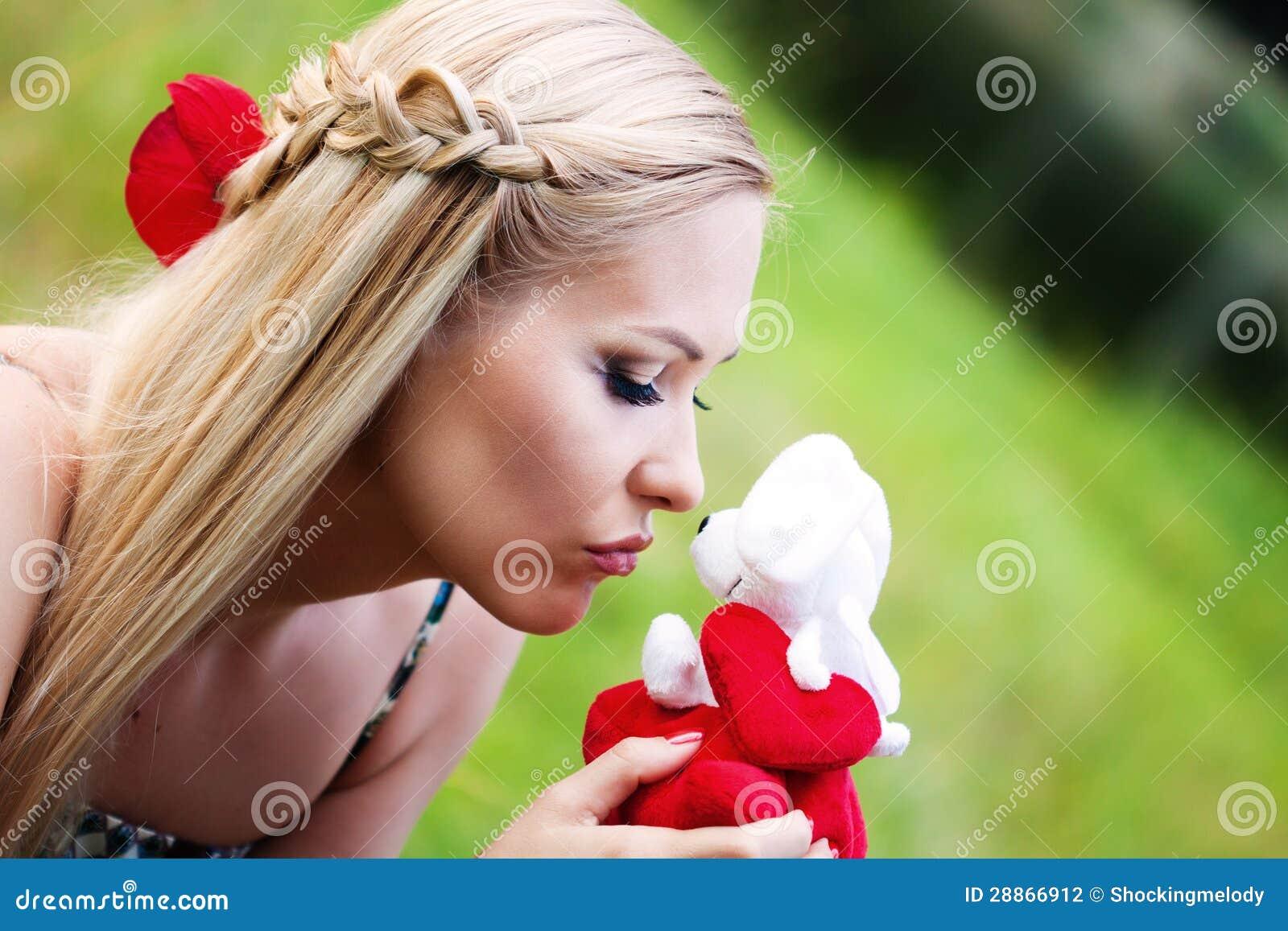 Blondes mädchen das ein spielzeug küsst stockfotografie