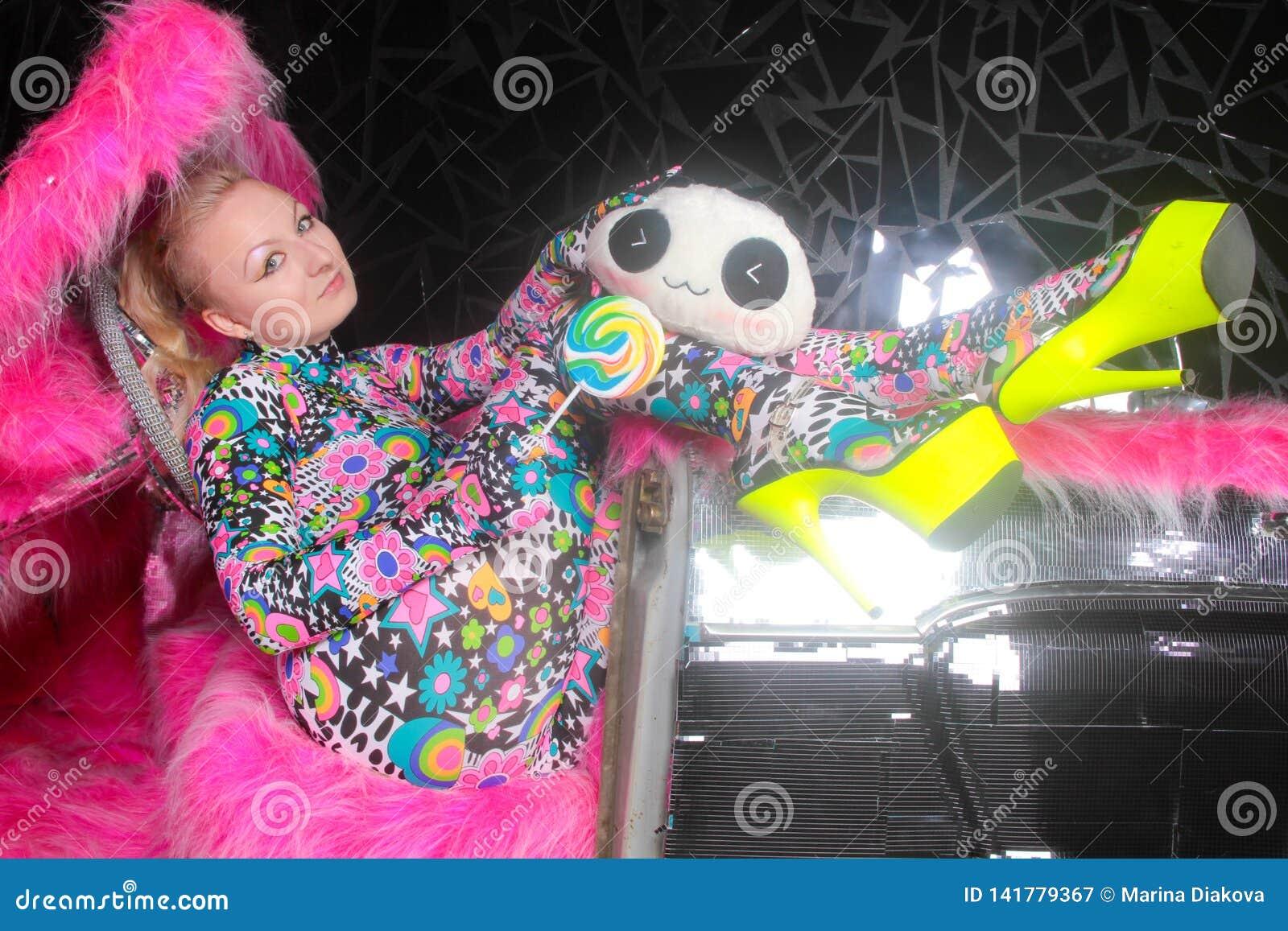 Blondes Mädchen der Vereinpartei in saurem Animeart Spandex catsuit mit Spiegelauto mit dem Rosapelz bereit zum verrückten Clubbi