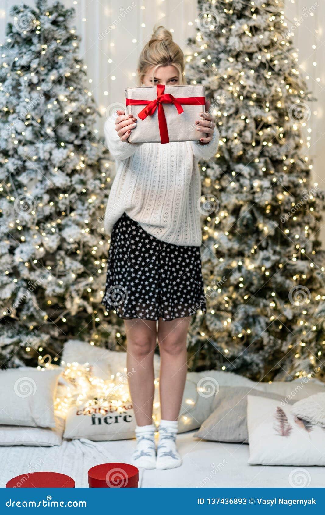 Blondes Mädchen in der weißen Strickjacke versteckt das Gesicht hinter dem Geschenk