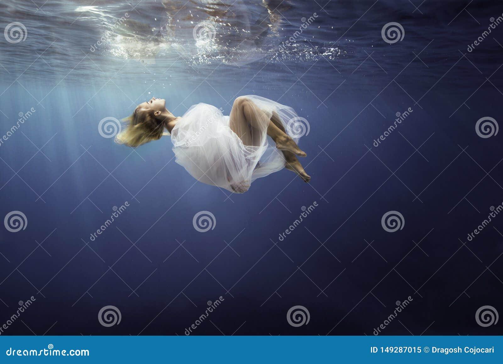 Blondes M?dchen wickelte in fine wei?en Stoff, sank in blaues tiefes Wasser von Ozean, gegen dunklen Seehintergrund ein