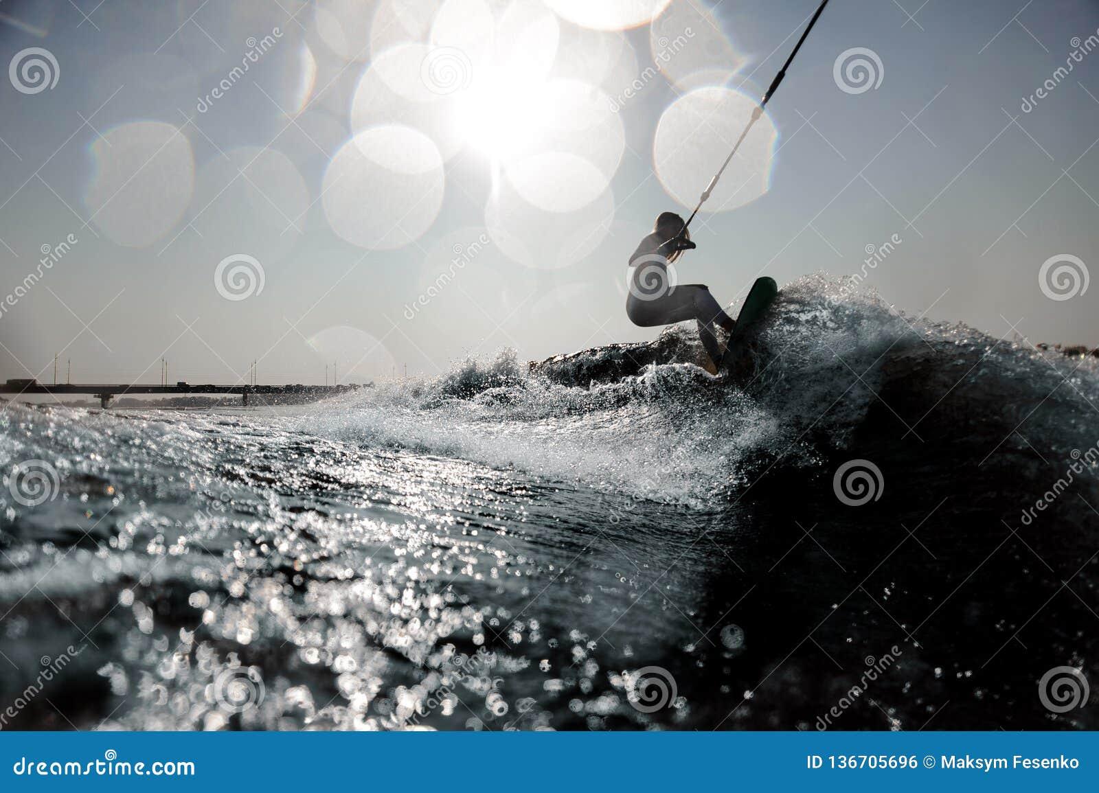 Blondes Mädchenreiten auf dem wakeboard, das ein Seil hält