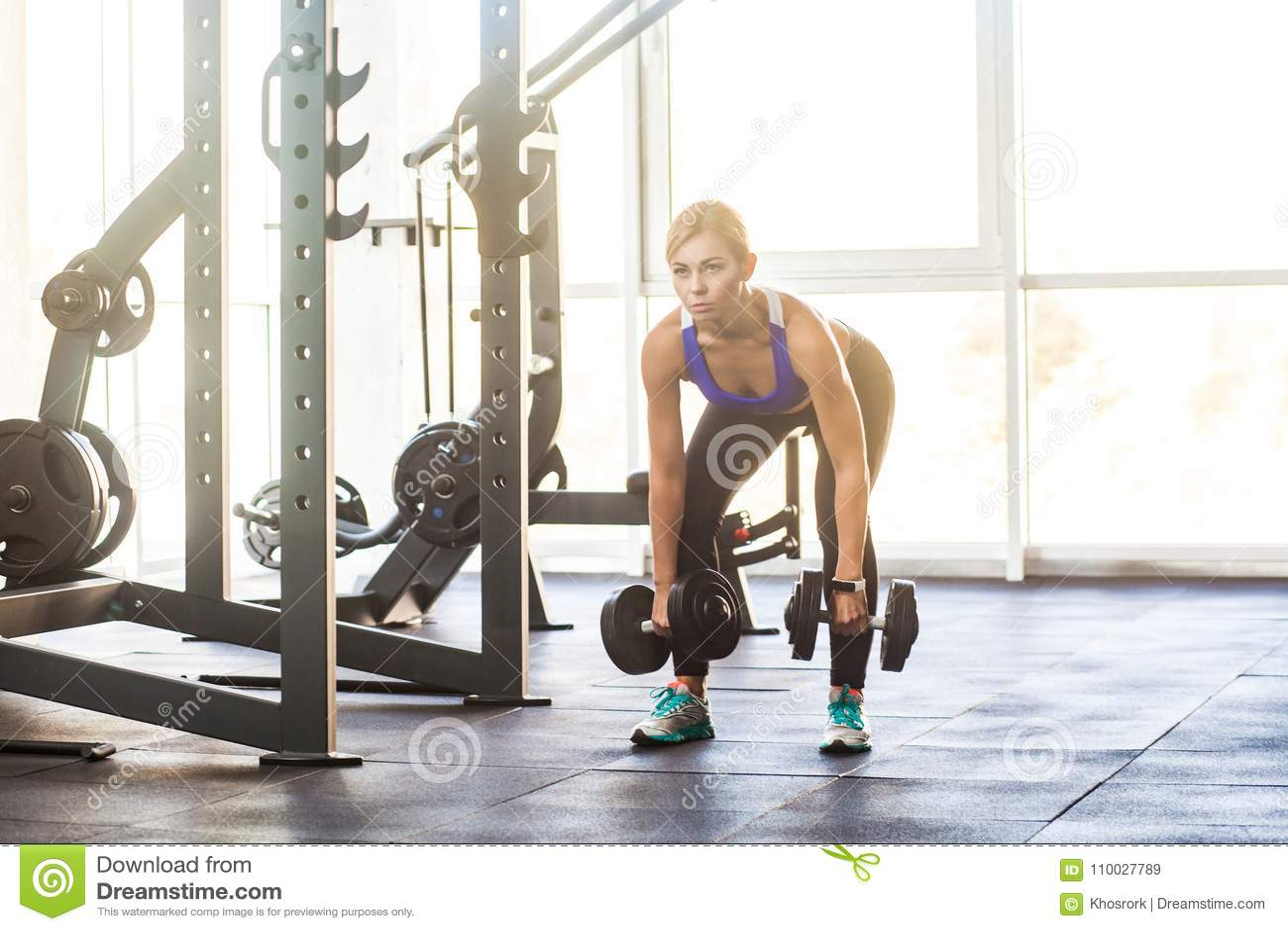 Blondevrouw in gymnastiek, schuine stand met domoren