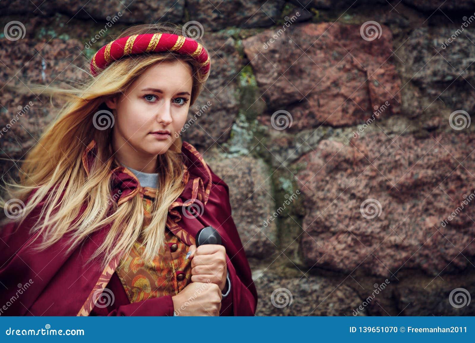 Blondevrouw stellen die zich met zwaard in rode kleren bevinden