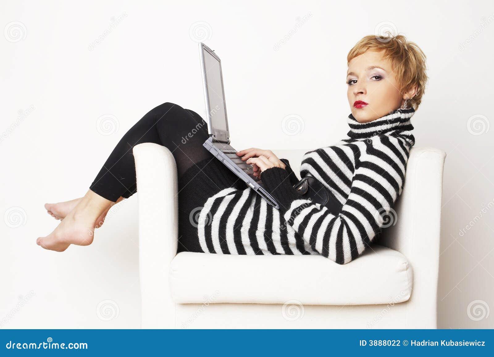 Blondgirl piacevole che si siede sulla presidenza con il computer portatile