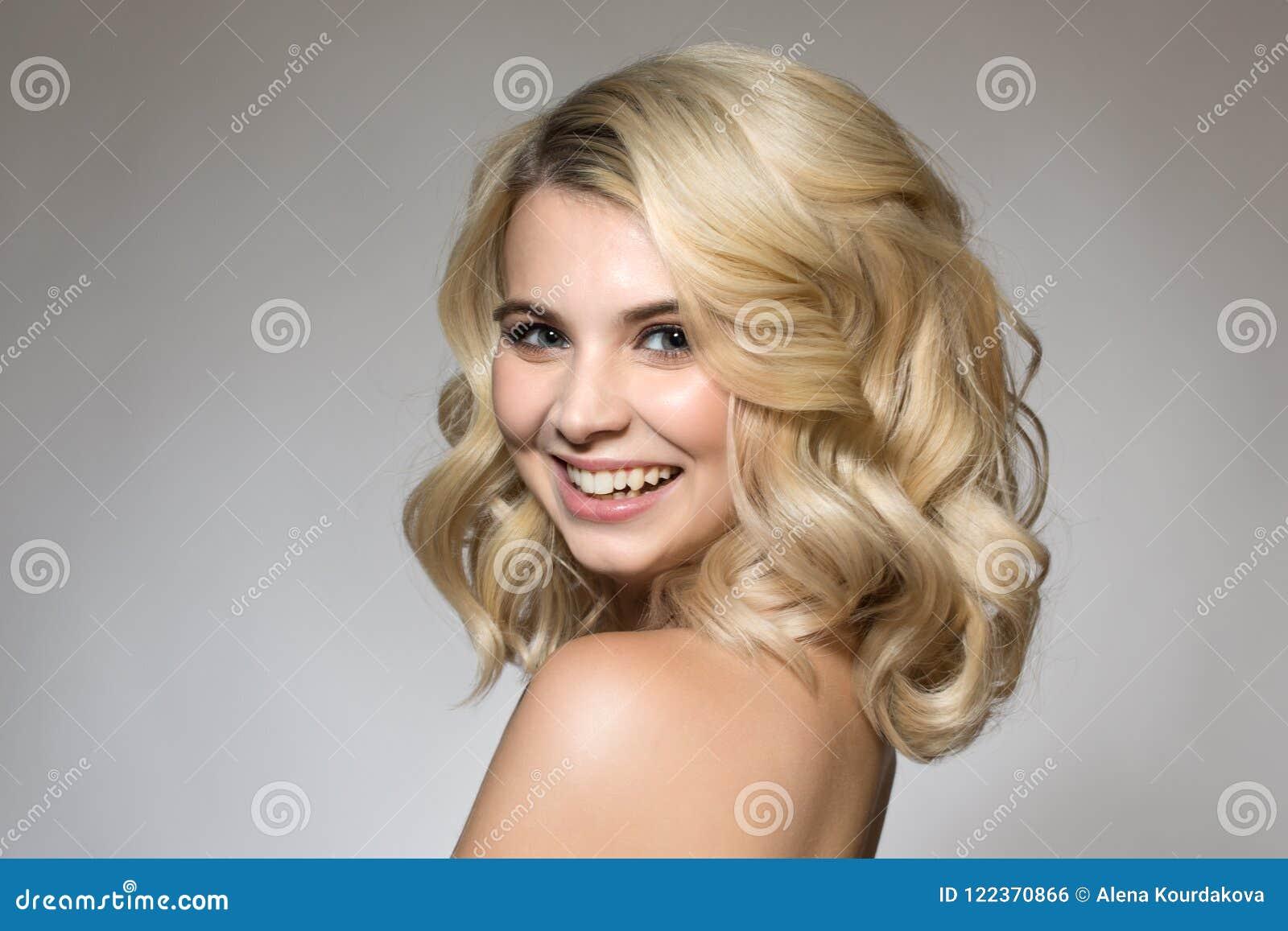 Blondin med krullning på en grå bakgrund, ett naturligt smink och en clea