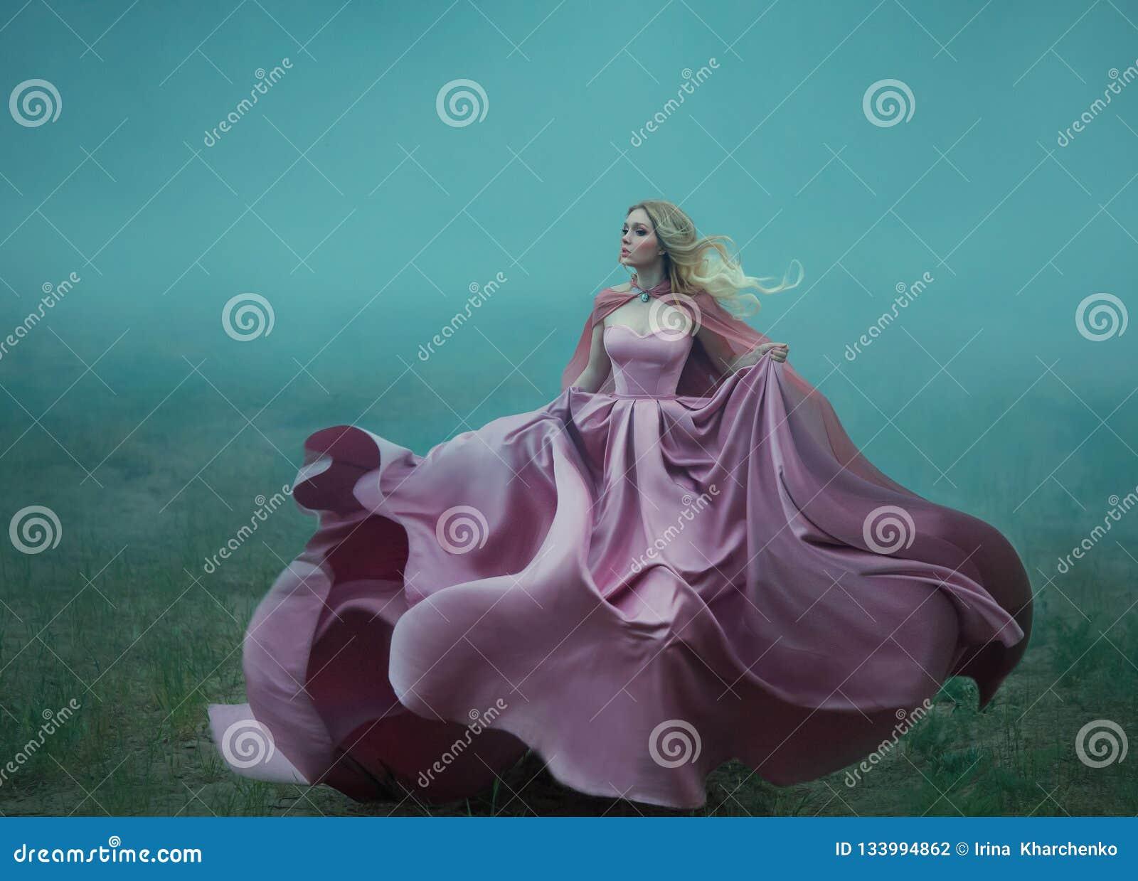 Blondinen i dimman i en ljus lång dyr kunglig klänning som fladdrar på - - fluga, tar formen av en magisk blomma, a