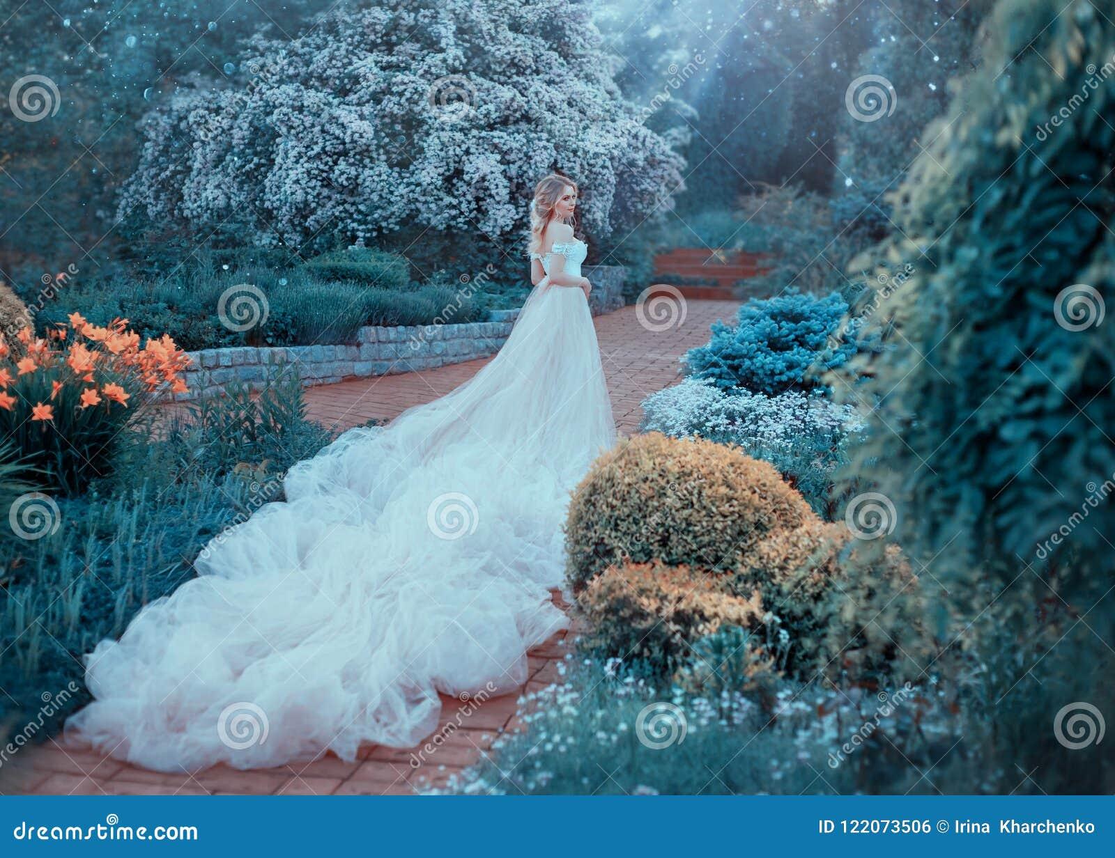 Blondinen med en härlig elegant frisyr, går i en sagolik blommande trädgård Prinsessa i ett lyxigt ljus - rosa färger klär