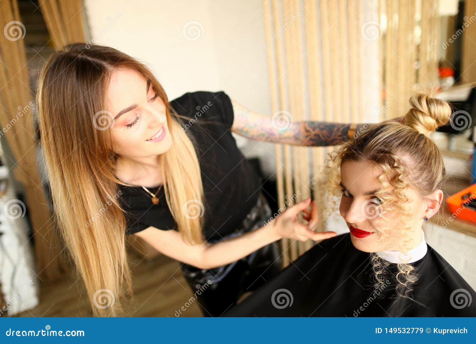 Blondynka fryzjer Robi fryzurze z kędziorami