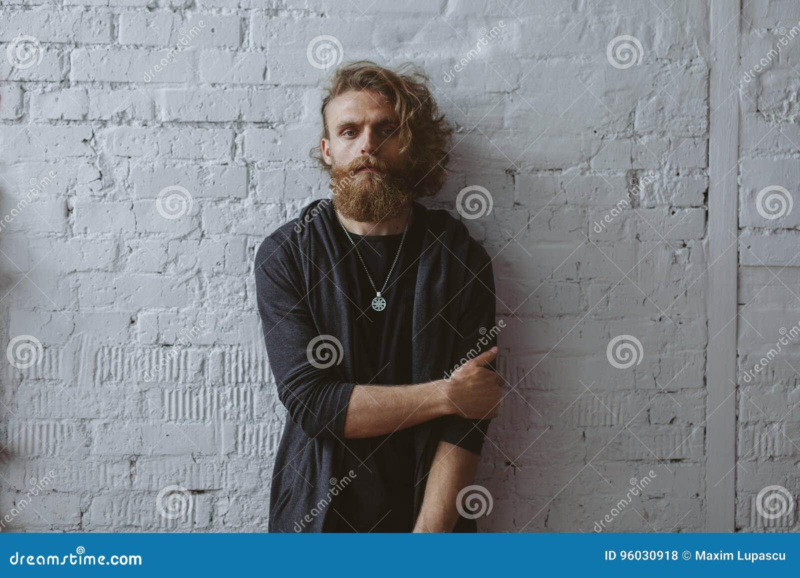 Blondynka mężczyzna brodaty kędzierzawy z włosami pozować