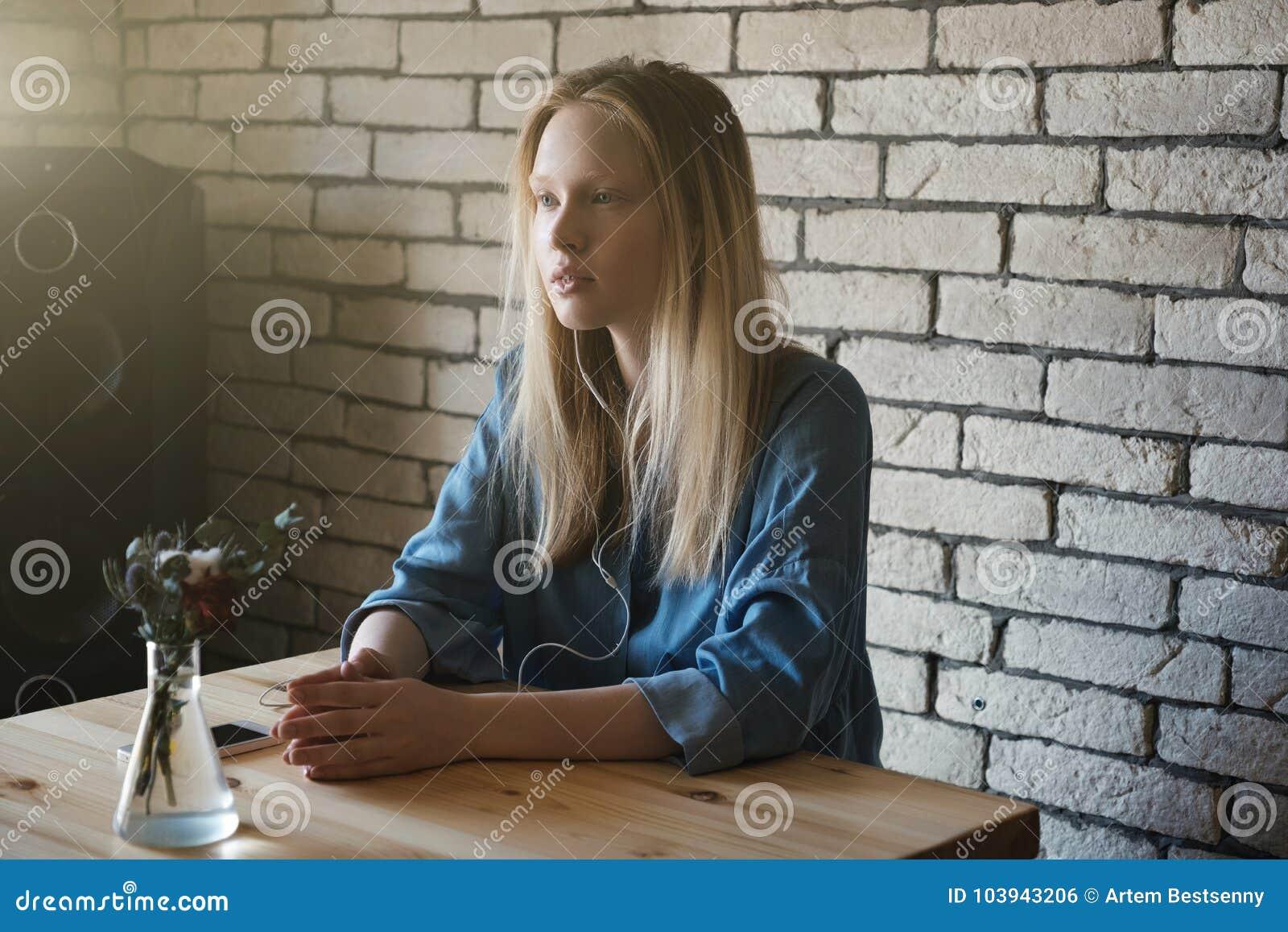 Blondynka siedzi z hełmofonami i przyglądającym zamyśleniem w odległość, stawia ona wpólnie ręka jon stół