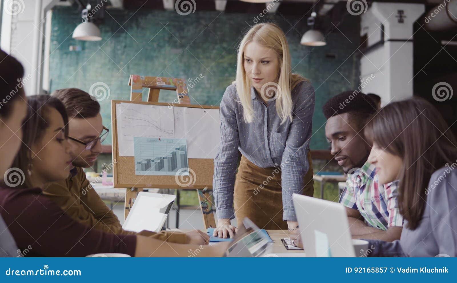 Blondynka zespołu kobiecego lider daje kierunkowi mieszana rasy drużyna młodzi faceci Kreatywnie biznesowy spotkanie przy nowożyt
