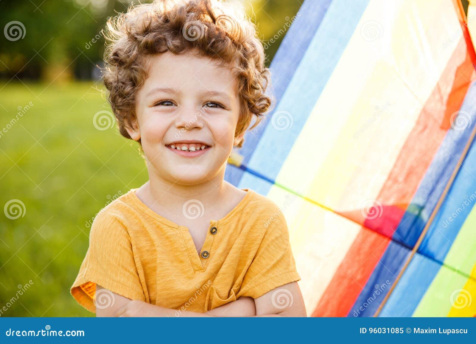 Blondynki chłopiec z ręka krzyżuję pozować outside