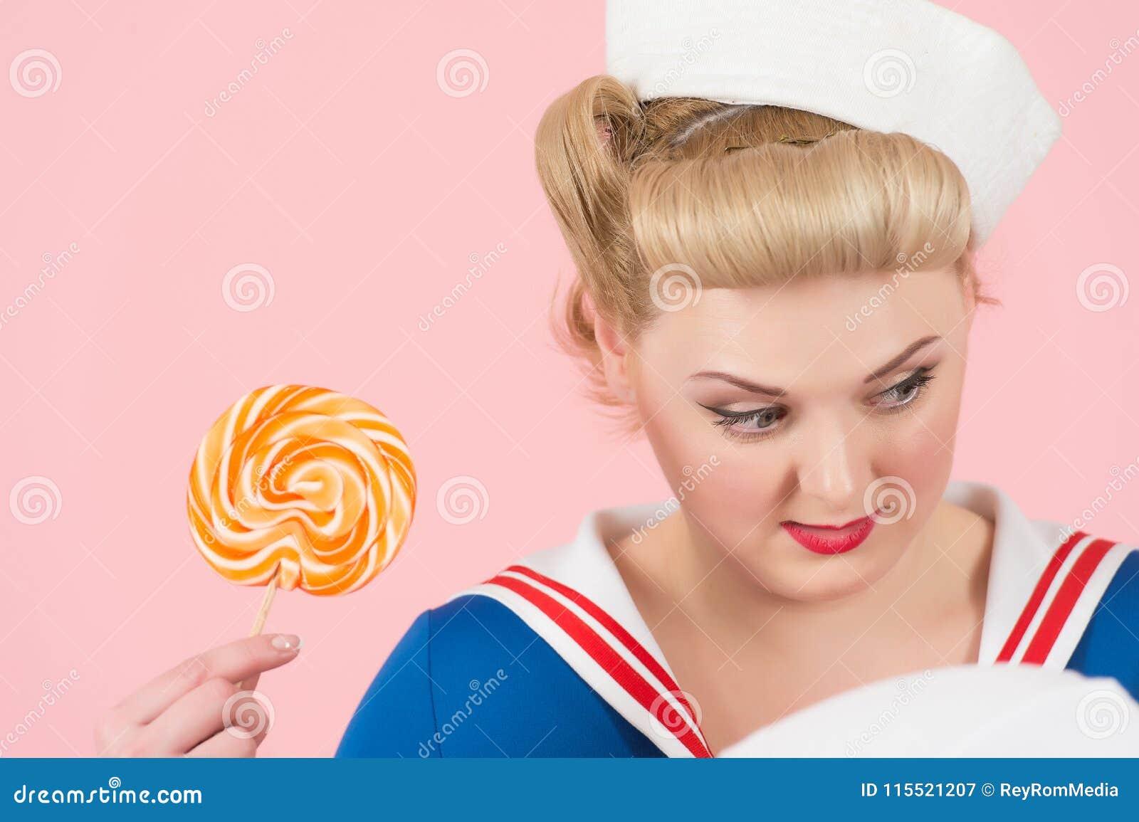 Blondynki dziewczyna i cukierki lizak Zamyka up cukierek kobieta na różowym tle