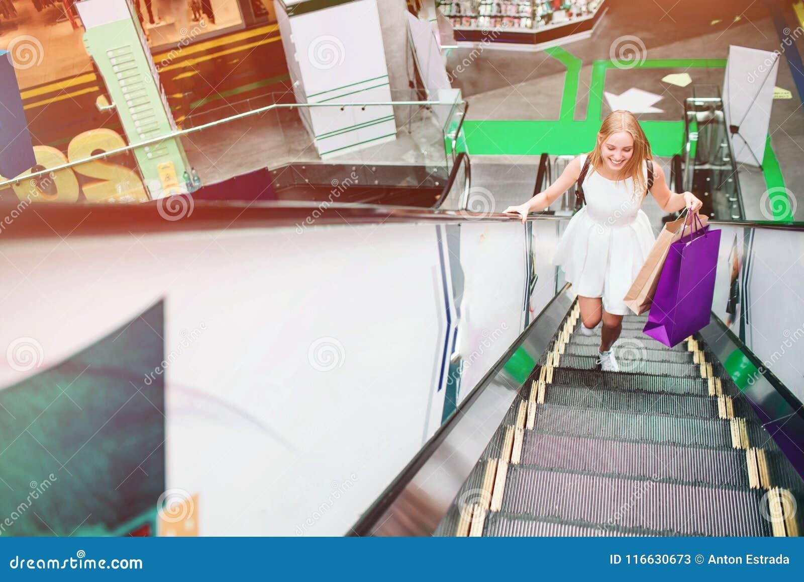 Blondynki dziewczyna jest działająca up na eskalatorze Fiołkowe torby w jej lewej ręce Jest w pośpiechu