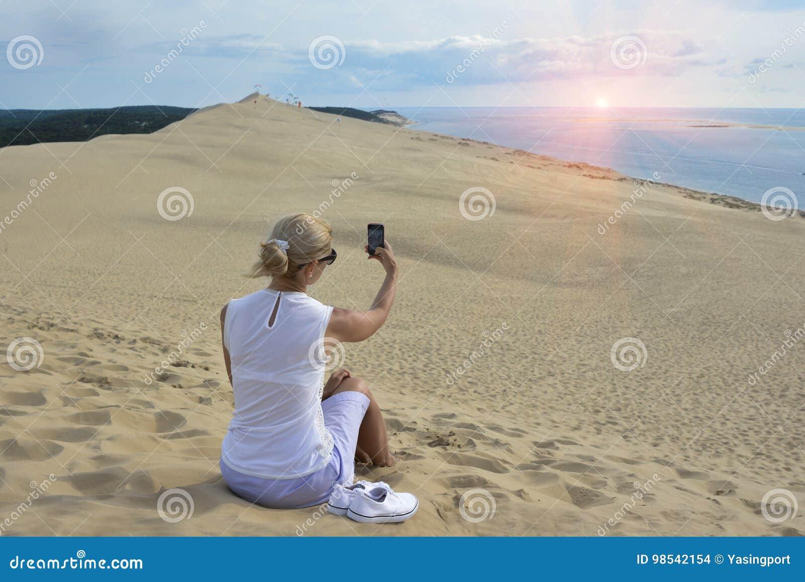 Blondynki dziewczyna robi selfie dla instagram przy Pyla diuną wielka piasek diuna w Europa