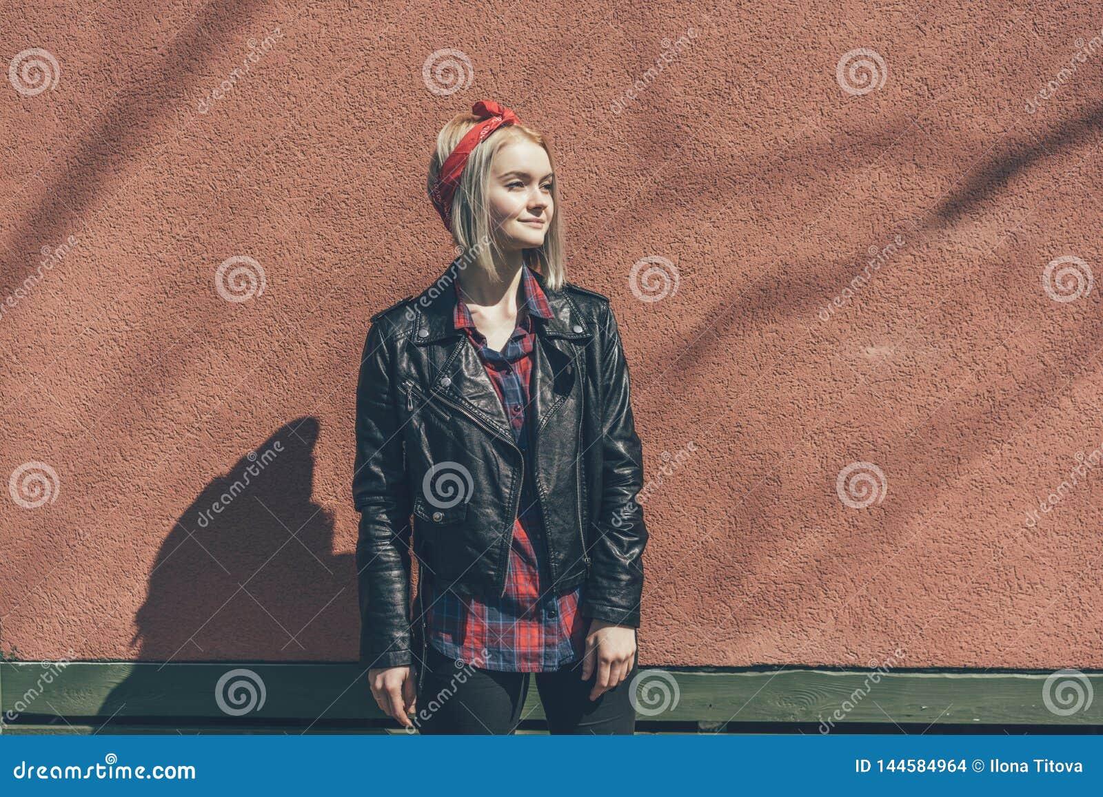 Blondynki dziewczyna w czerwonym włosianym bandażu i czarnej skórzanej kurtce