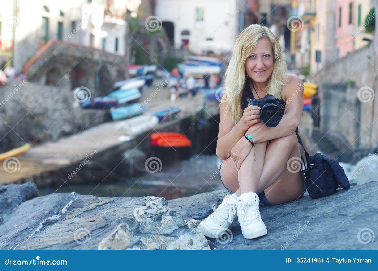 Blondynki dziewczyna z kierowym wristband siedzi na skale i trzyma kamerę przy Riomaggiore, los angeles Spezia, Włochy