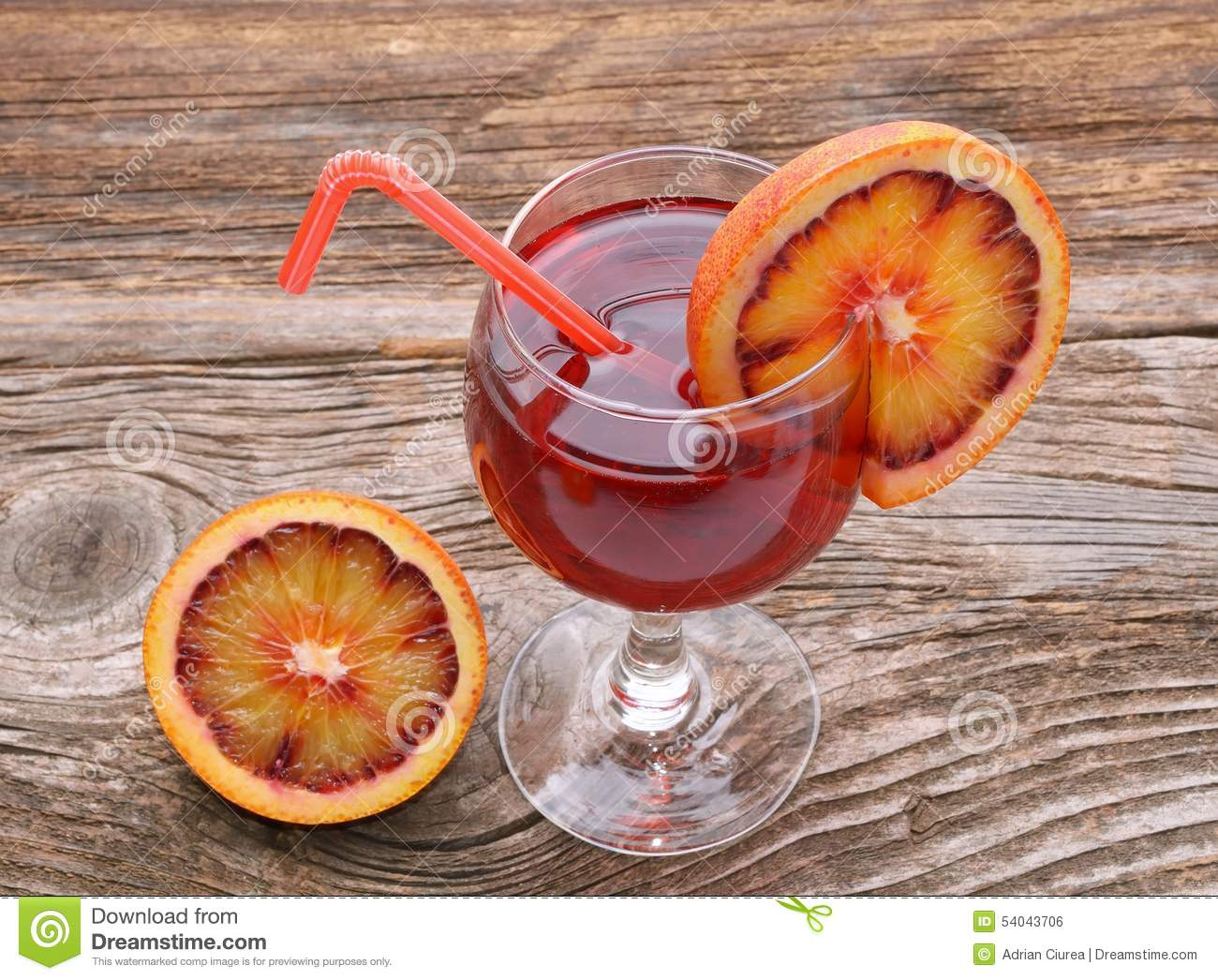 Blood orange cocktail with slices of blood orange on wooden table