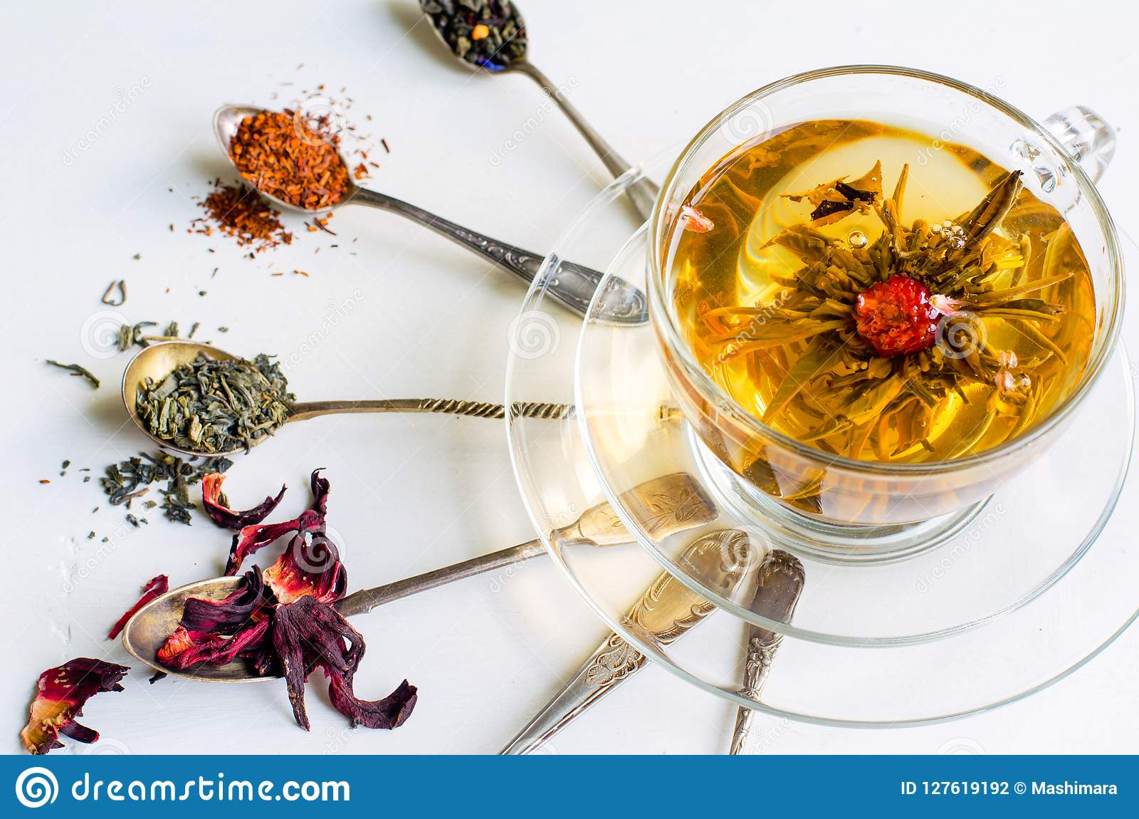 Blooming or flowering tea in a glass cup and spoons with various kinds of tea on white background