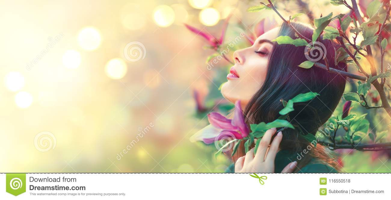 Blooming magnolia trees. Beauty young woman touching and smelling spring magnolia flowers