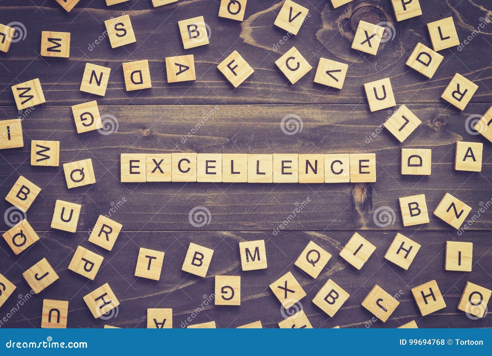 Bloque de madera de la palabra de la excelencia en la tabla para el concepto del negocio