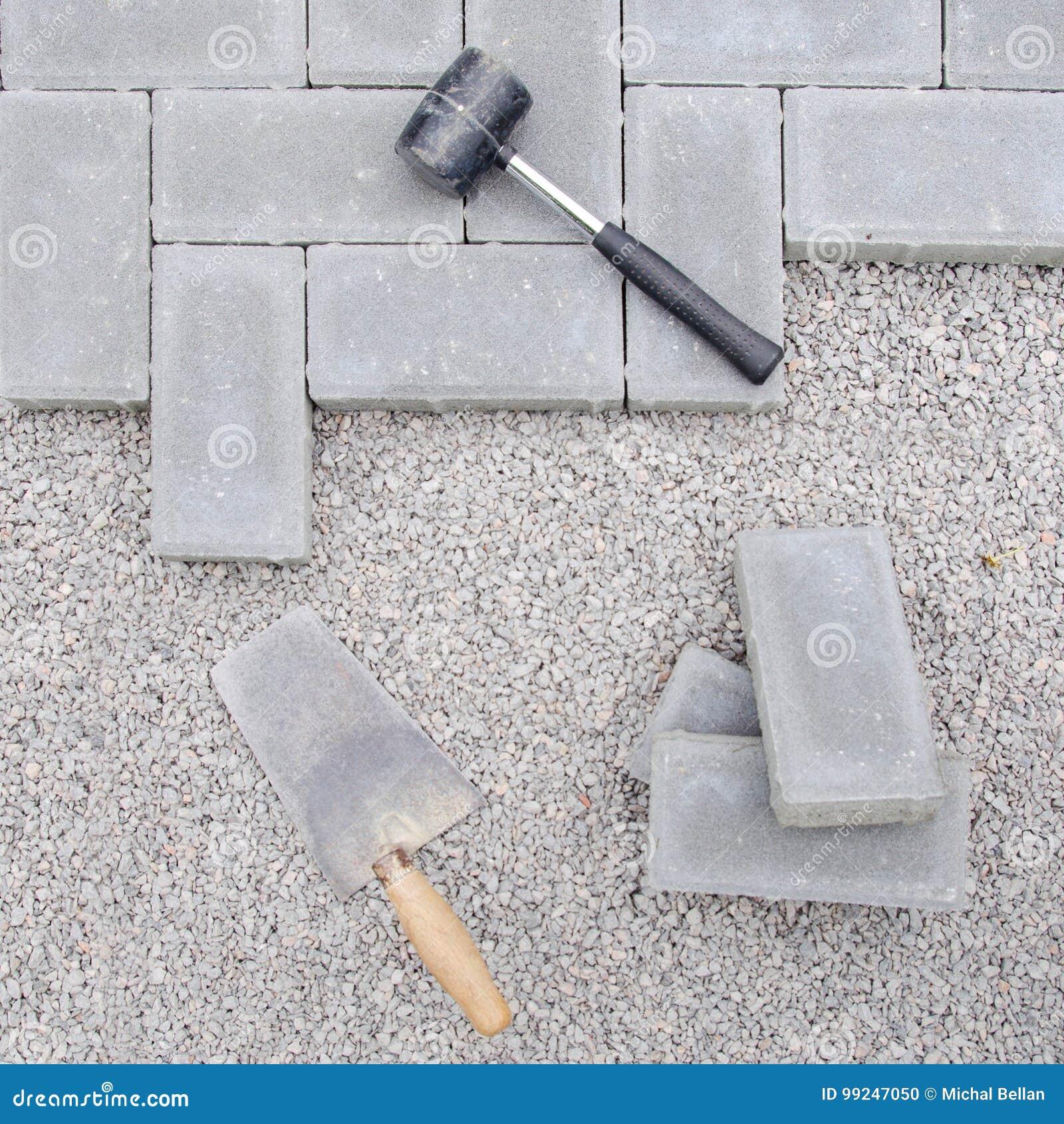 Bloques de la piedra con la herramienta para pavimentar el fondo de la fijación Concepto del arquitecto de Hausework