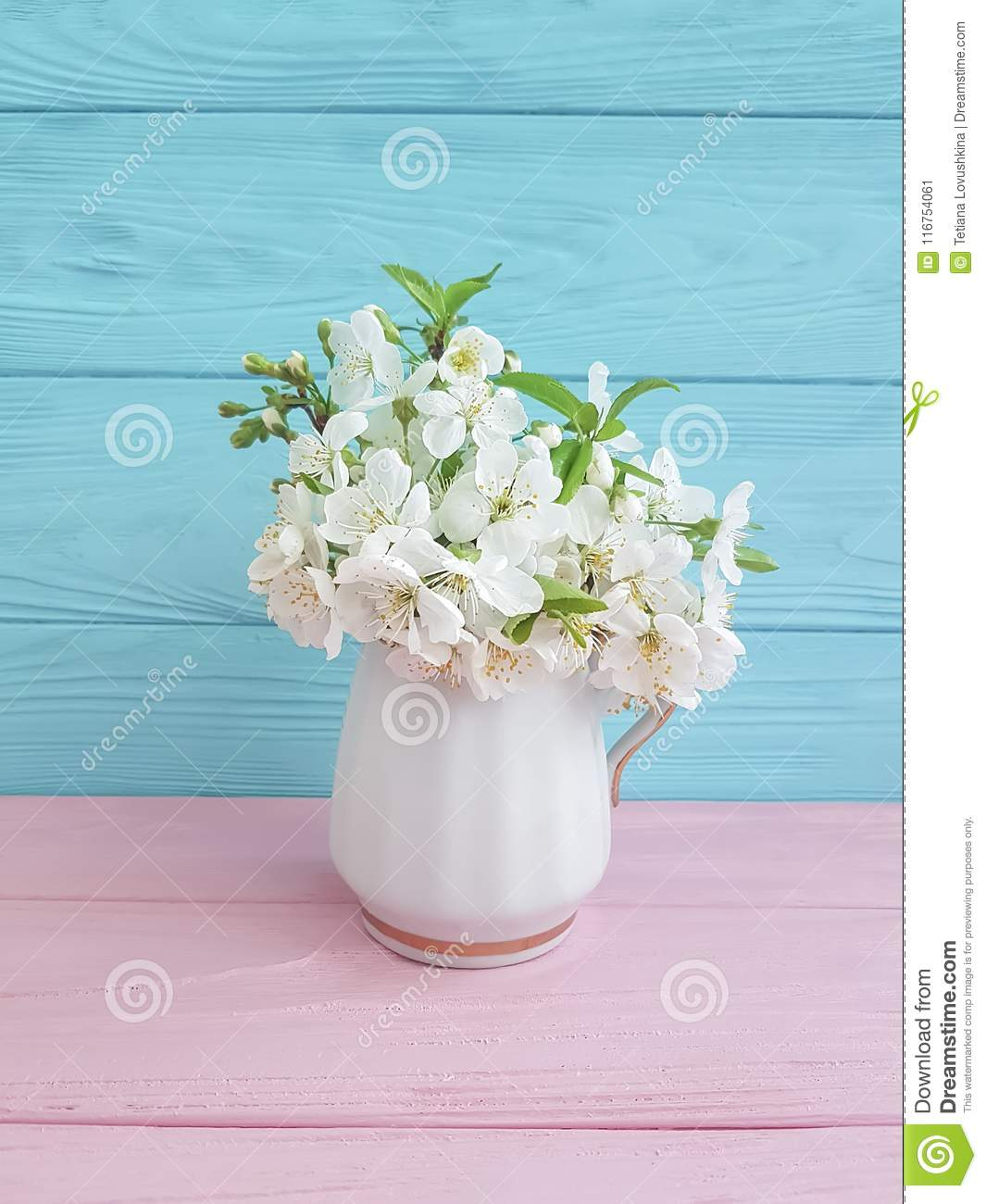Blossoming cherry springtime vase bouquet on a wooden background