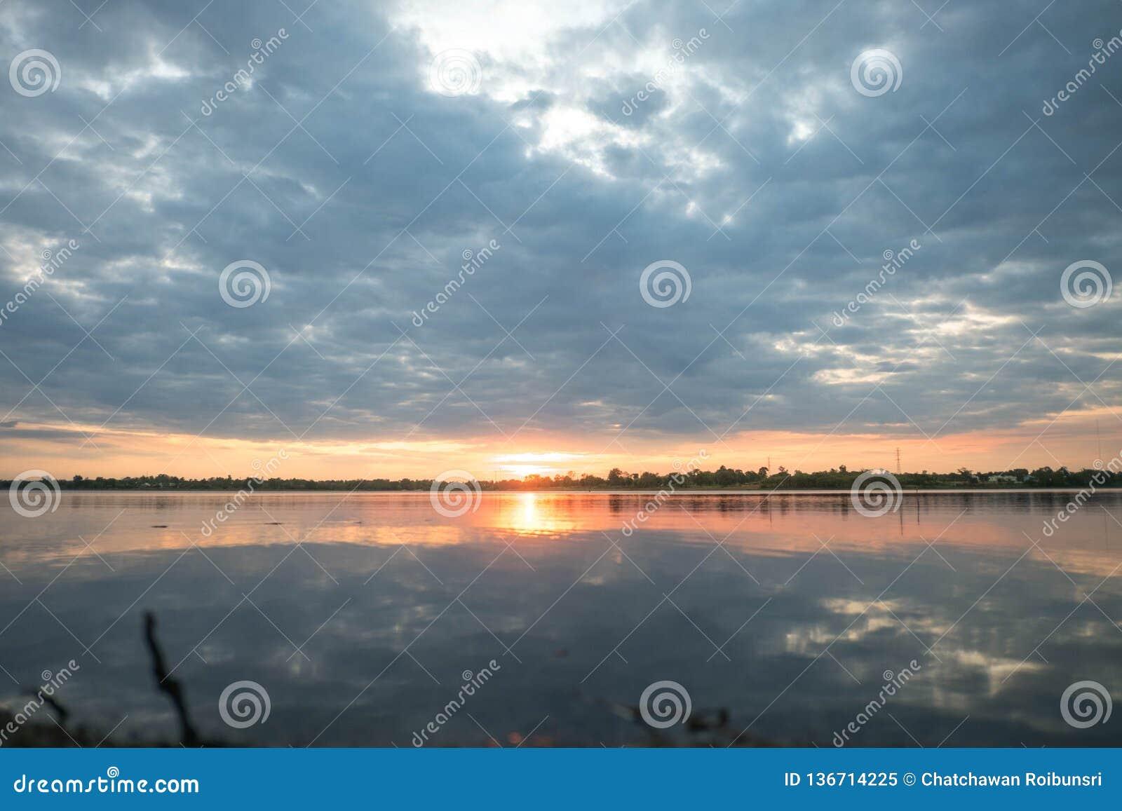 Blu scuro - l arancia con le nuvole al tramonto il sole arancio cade dietro l orizzonte Dietro lo sfondo naturale di scene