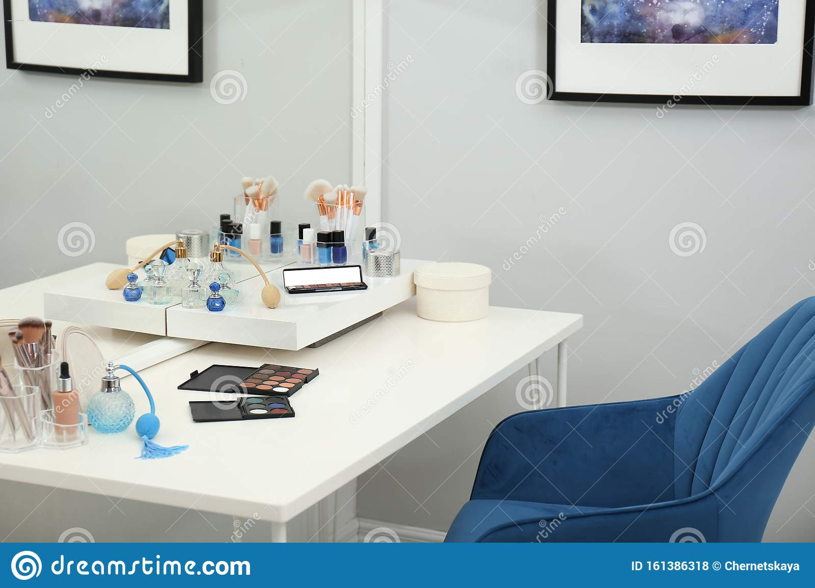 Blue Armchair Near Dressing Table With Makeup Products Stock Photo