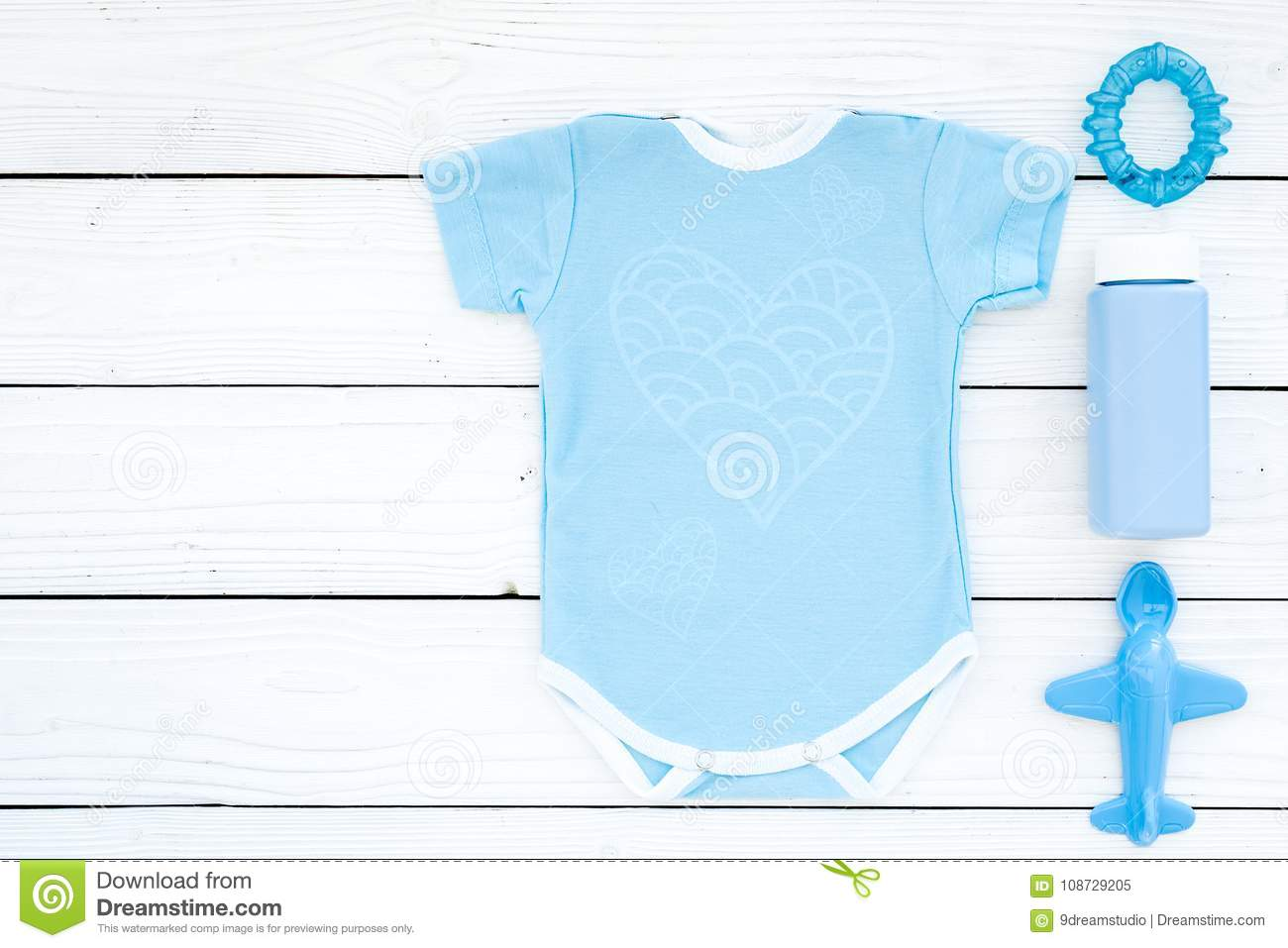Blue baby clothes for little boy. Bodysuit, toys, cosmetics on white wooden background top view copy space