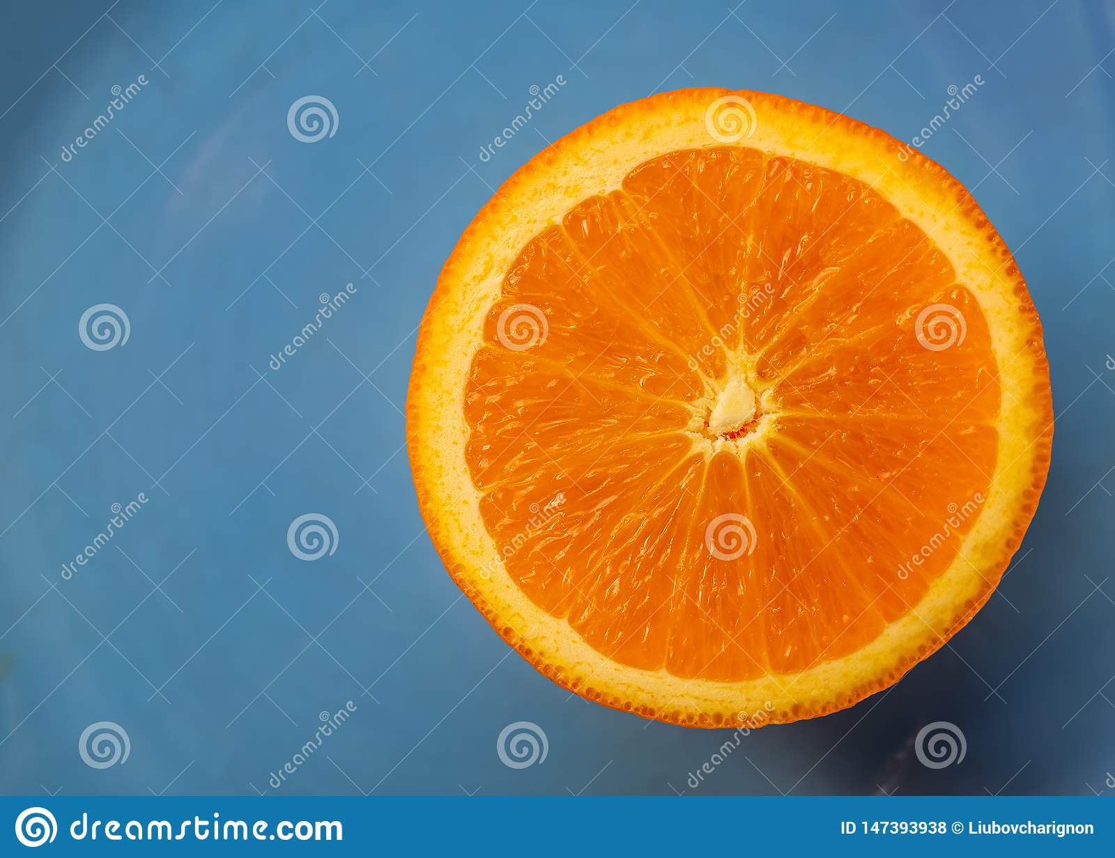 Blue background with fruit citrus an orange or half  tangerine. Macro image and close-up, concept for healthy food.