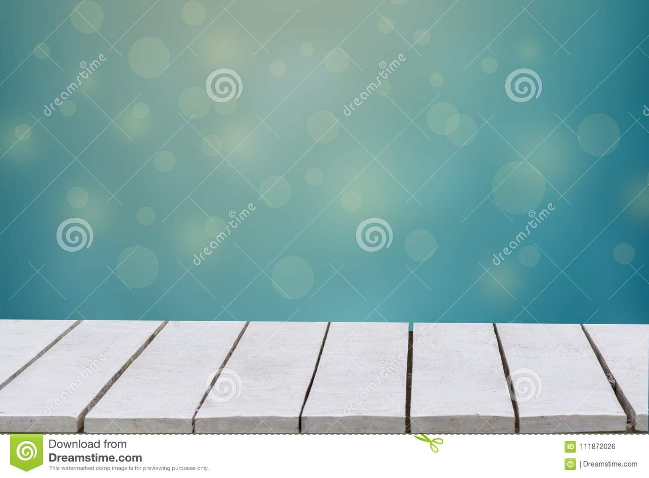 Blue background with selective focus. The green background has a bokeh leaf and grass on a white wooden floor. Empty table empty s
