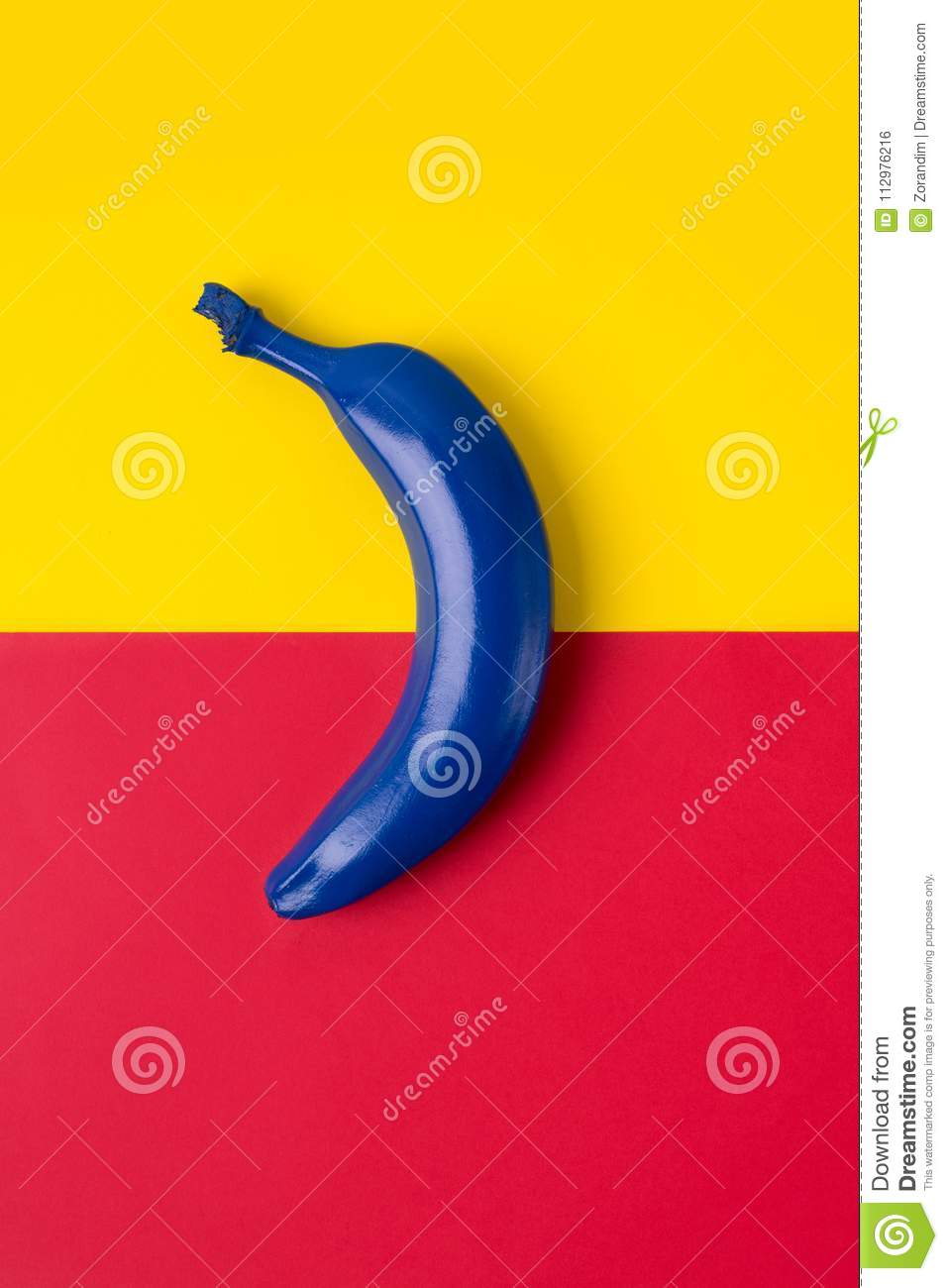 Blue banana on the bright background of red and yellow colors. Top view image
