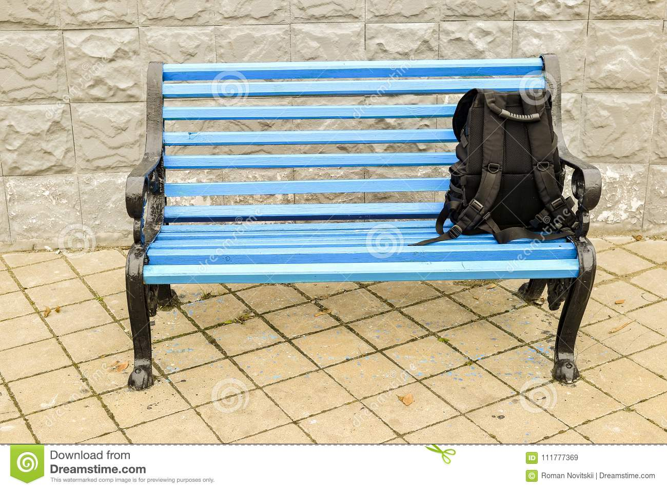 The blue bench in the Park on the tiled pavement with a black backpack. No body.
