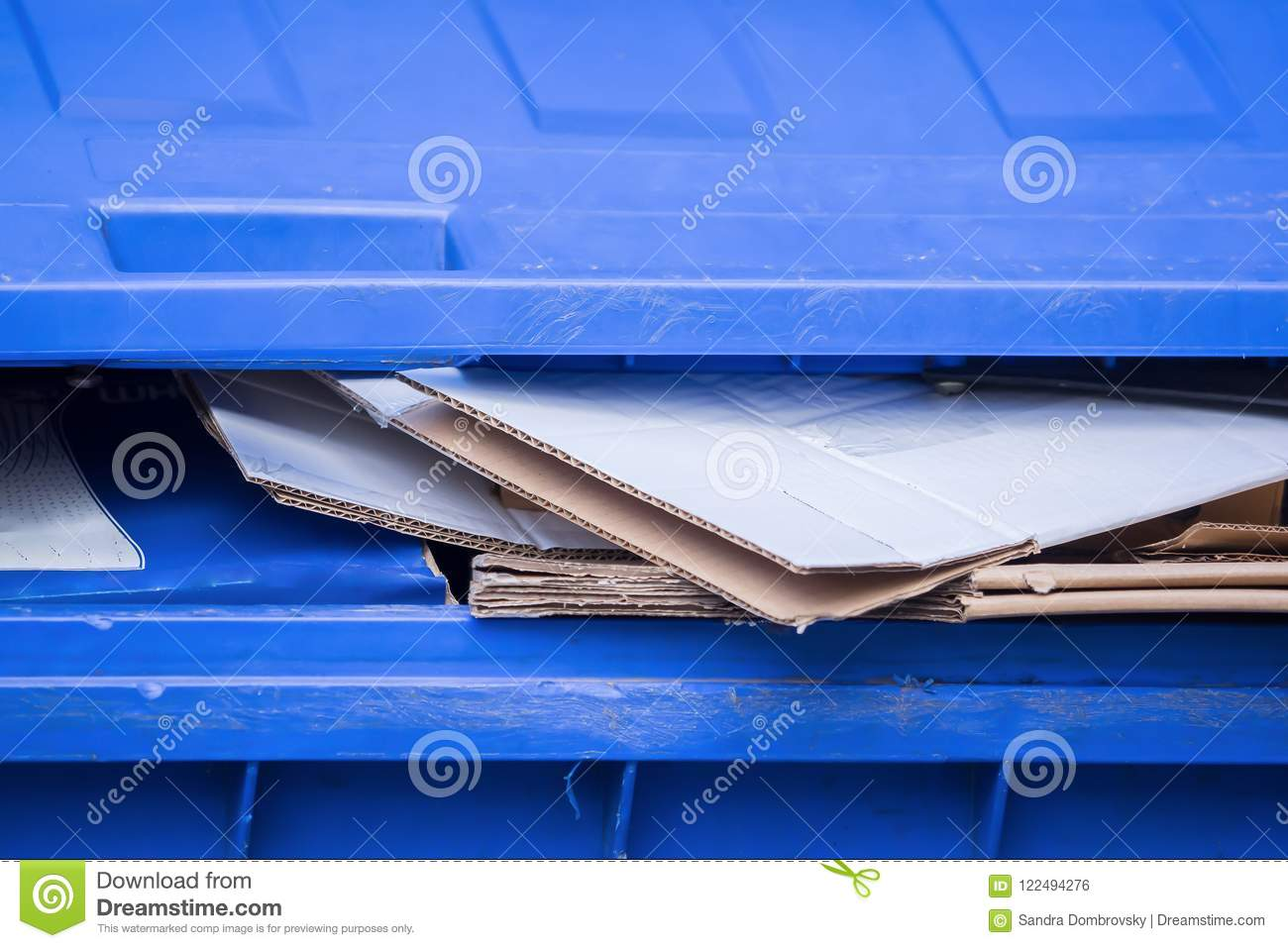 A blue bin for old paper and cardboard boxes