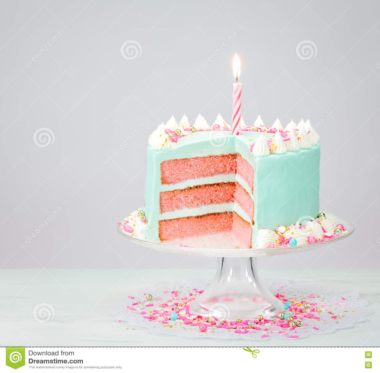 Pastel Blue Birthday Cake Over White Background With Pink Layers And Sprinkles