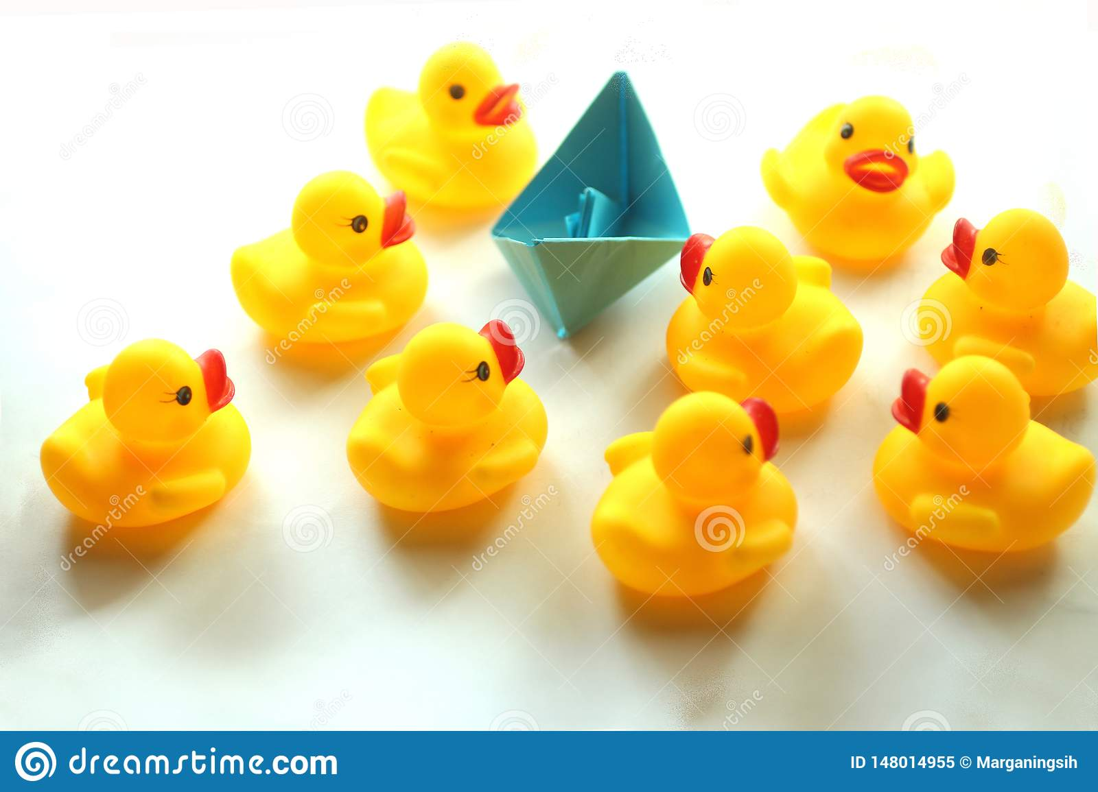 Cute yellow rubber ducks and blue paper ship.
