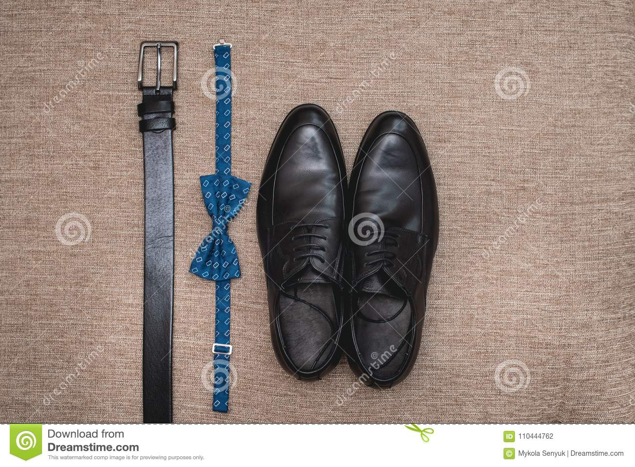 c8c1e5128fef Blue bow tie, leather black shoes and belt. Grooms wedding morning. Close  up of modern man accessories. Look from above