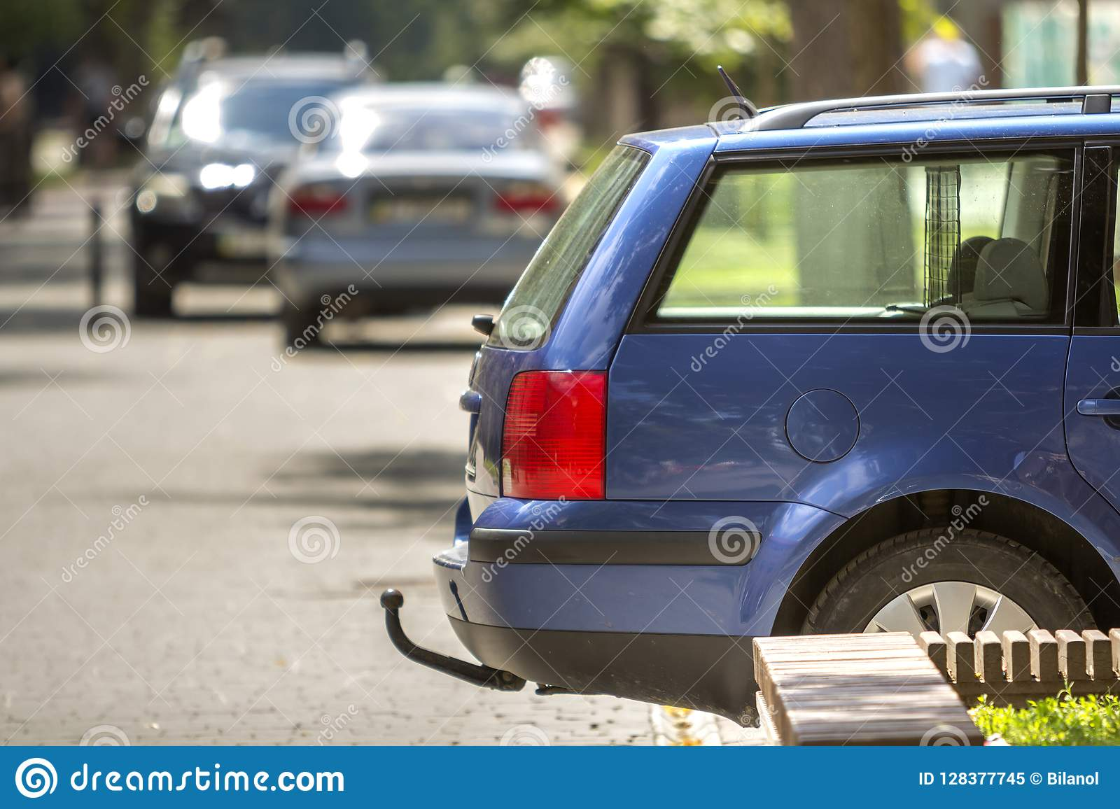 blue car parked on sunny street, red stop lights, hook for