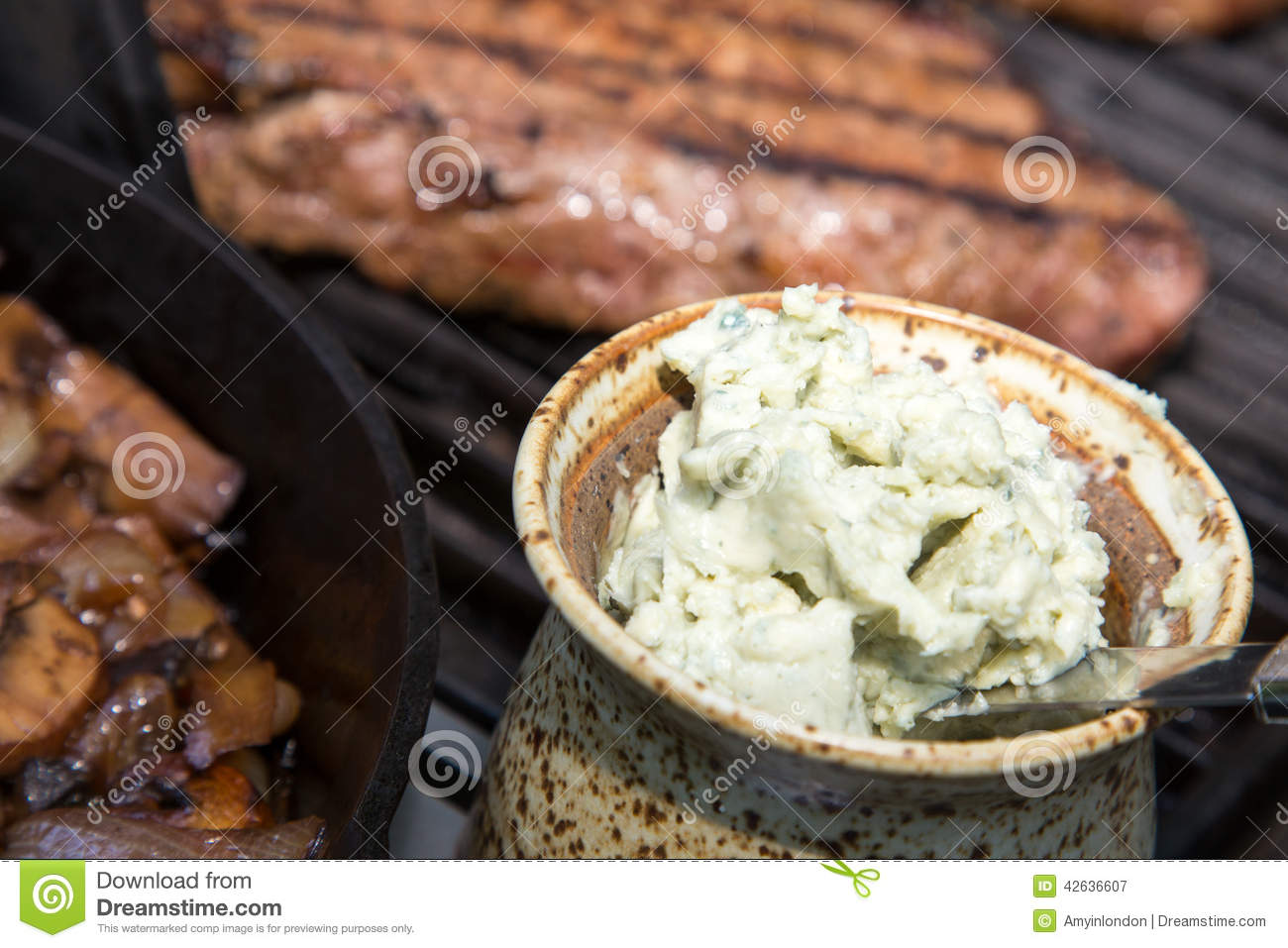 Close up of Home made crock of blue cheese steak butter with steaks on ...