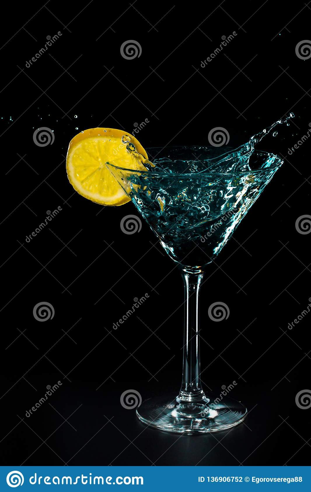 Blue cocktail water drink splash in the glass with lemon Isolated on black